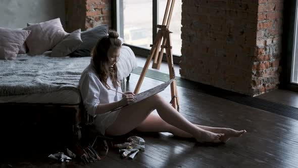 Thumbnail for Painter Paints a Picture Sitting on the Floor in a Home Studio. Girl in a Man's Shirt