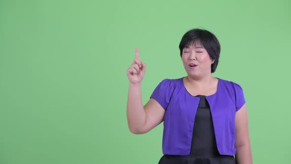 Thumbnail for Happy Young Overweight Asian Woman Pointing Up and Looking Surprised