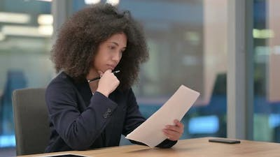 African Businesswoman Reading Documents at Work