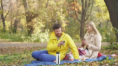 Romantic Couple Sitting in the Park in Autumn on a Sunny Day, Happy Together, Smiling and Drinking