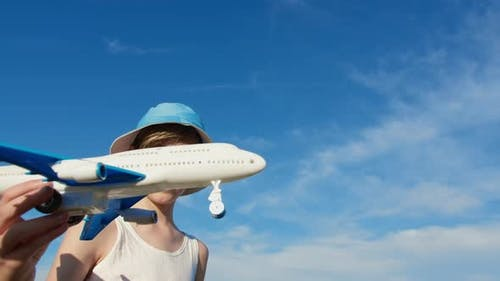 Boy in a Hat Playing with Airplane on Sky Background, Boy Wants To Become a Pilot