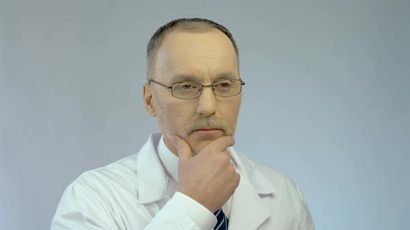 Thumbnail for Serious Male Doctor Touching Face While Thinking, Finding Solution, Good Idea