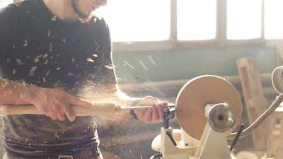 Attractive Carpenter Working on Woodworking Lathe Machine in The Carpenter Workshop.