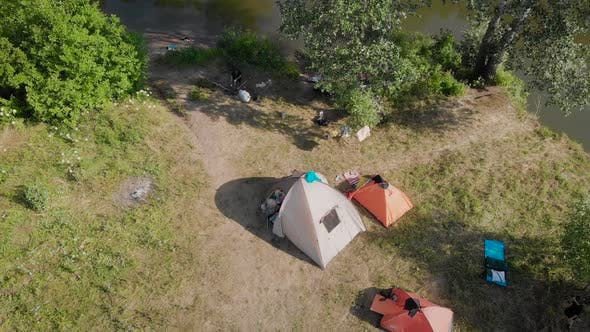 A Small Camp in the Fields. Tourists Stopped in a Beautiful Natural Place with Three Tents, Cook