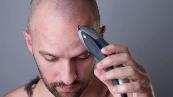 Thumbnail for A Man Shaves His Head with a Hair Clipper