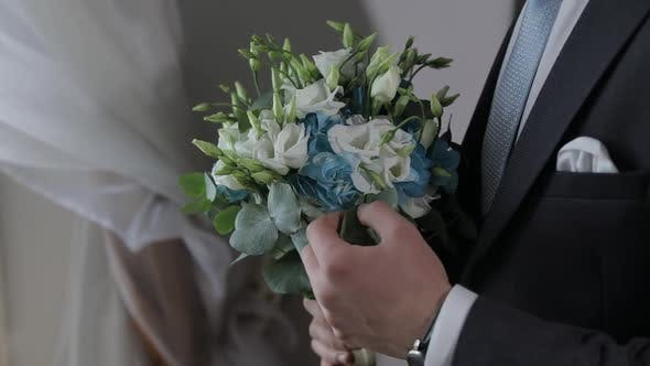 Thumbnail for Groom with Wedding Bouquet in His Hands at Home. White Shirt, Blue Tie, Jacket