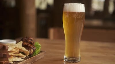 Closeup View of beer and snacks. A glass with beer and snacks on a plate on wooden table