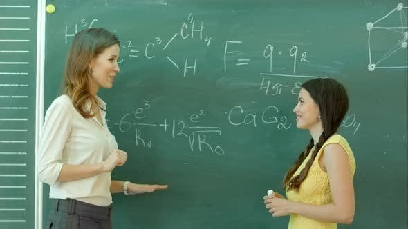 Thumbnail for Pretty Young Female College Student Writing on the Chalkboard Blackboard During a Chemistry Class