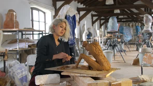 Sculptor is Sculpting a Realistic, Figurative Model in Large Studio
