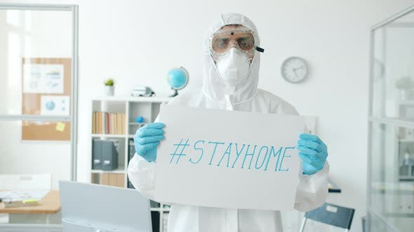 Portrait of Man in Quarantine Suit Standing in Empty Office with Stayhome Banner