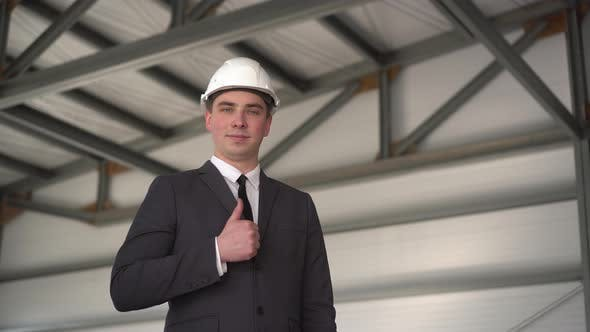 A Young Man in a Protective Helmet, Shows a Thumb at a Construction Site. The Boss in a Suit Looks