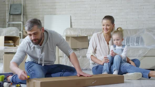 Thumbnail for Girl Helping Father Opening Package