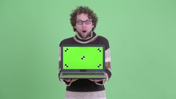Thumbnail for Happy Young Bearded Man Showing Laptop and Looking Surprised