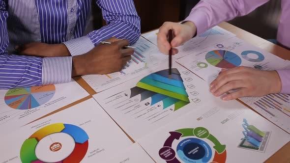 Businessmen discuss infographics