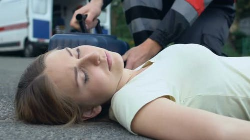 Unconscious Woman Lying on Asphalt, Paramedic Rendering First Medical Assistance