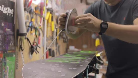 Thumbnail for Repairman Doing Waxing And Ironing. Snowboard Maintenance And Repair Concept.