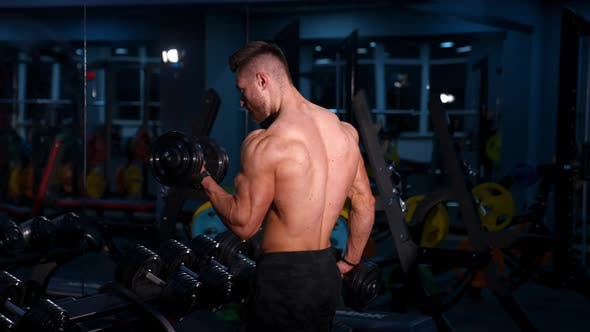 Fit young man lifting dumbbells doing workout at a gym.