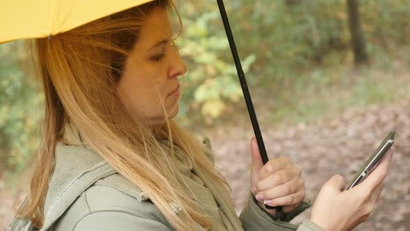 Blonde female outdoor using mobile phone while raining 4K 3840X2160 UltraHD footage - Blond woman wi
