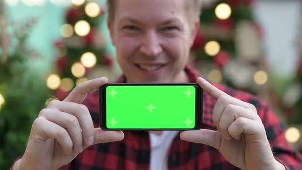 Thumbnail for Young Happy Hipster Man Showing Phone Against Christmas Trees Outdoors