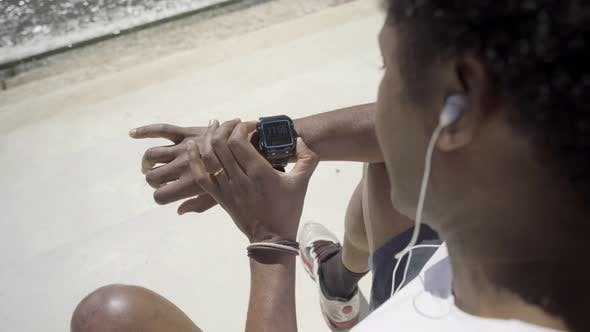 Cover Image for Focused African American Man Setting Sport Watch