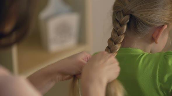 Thumbnail for Big Sister or Babysitter Braiding Little Girl's Hair, Woman Taking Care of Child