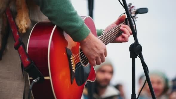 Cover Image for A Man Playing Guitar on Stage on the Festival