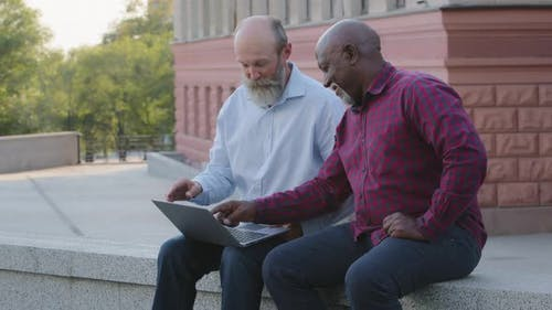 Two Funny Elderly Men Sitting Outdoors Using Laptop Finding Bug Getting Negative News