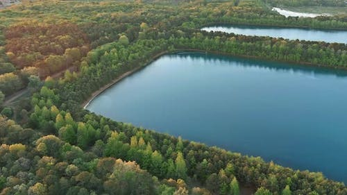 Beautiful Spring Nature Landscape with a Lake Between Green Forest