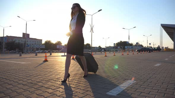 Thumbnail for Woman in High Heeled Footwear Walking Near Airport Parking with Her Luggage at Sunset Time