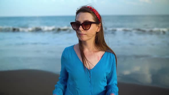 Thumbnail for Portrait of a Woman in a Beautiful Blue Dress on a Black Volcanic Beach. Slow Motion