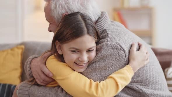 Thumbnail for Laughing Caucasian Girl Hugging Granddad at Home