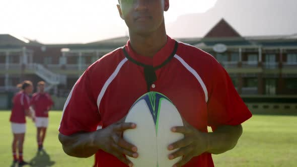 Male rugby player standing with rugby ball on the rugby ground 4k