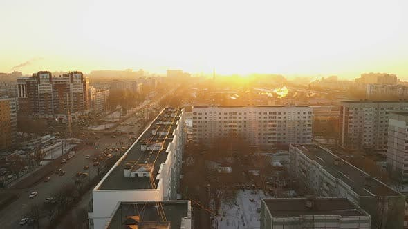 An Aerial View of the Winter City. Homes and Moving Cars in the Bright Sun