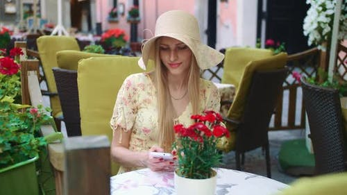 Woman Browsing Smartphone in Outside Cafe. Cheerful Young Lady Sitting at Table in Outside