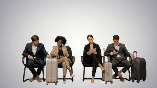 Diverse business travelers sitting in waiting area of airport