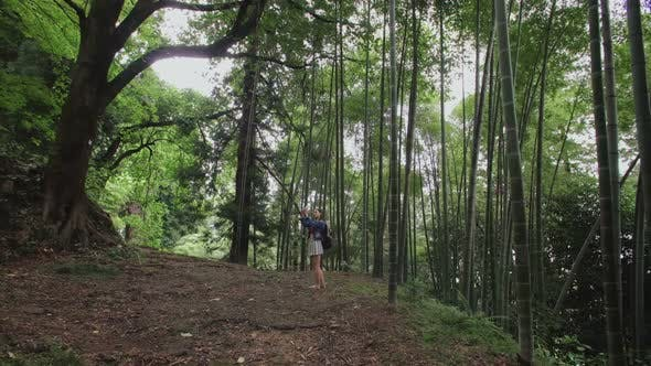 Thumbnail for European Girl Traveler Takes Photo on Smartphone in Tropical Forest Trees Bamboo Plantation