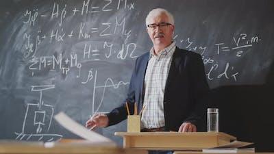 Senior Professor Posing for Camera beside Chalkboard