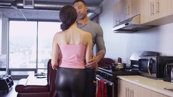 Thumbnail for Black and Latin couple holding each other romantically in kitchen of apartment