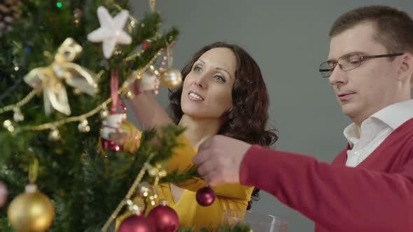 Romantic couple decorating Christmas tree, enjoying mutual pastime at home