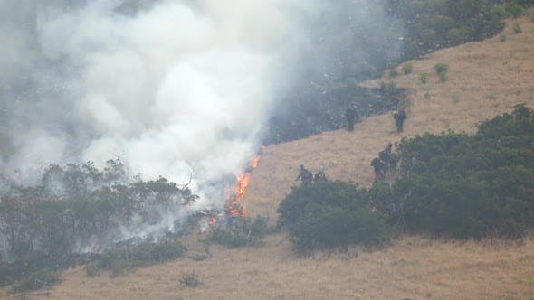 Thumbnail for Wildfire burning on mountain as firefighters control the blaze