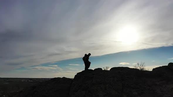 Silhouette of a Man Walking Along a Ridge