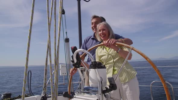 Thumbnail for Senior couple behind the wheel of sailboat together. Shot on RED EPIC for high quality 4K, UHD, Ultr