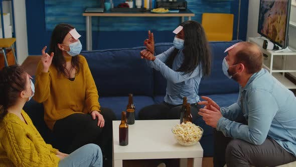 Diverse Friends with Face Mask Playing Games with Sticky Notes on Forheads