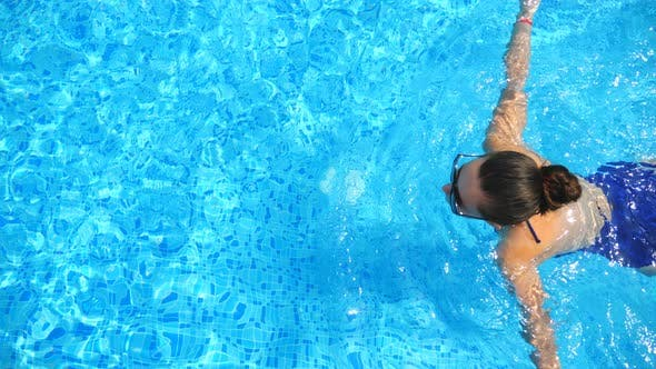 Thumbnail for Woman in Sunglasses Swimming Through Pool with Crystal Clear Water. Elegant Girl Relaxing on