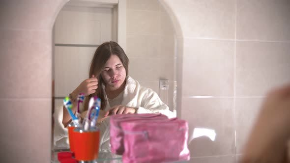 Thumbnail for A Young Woman Brushes Her Hair Looking in the Mirror