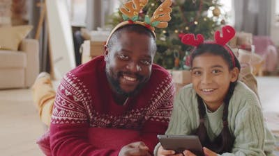 Portrait of Happy Black Dad and Daughter in Christmas Headbands