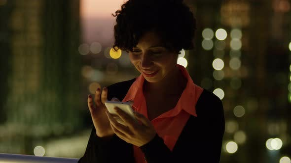 Thumbnail for Woman using cell phone at night in city