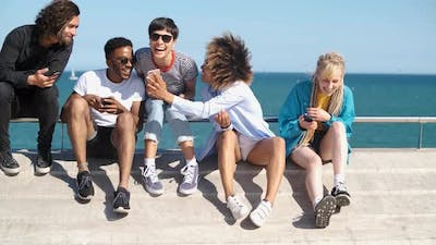 Young Diverse People with Mobile Phones on Seafront