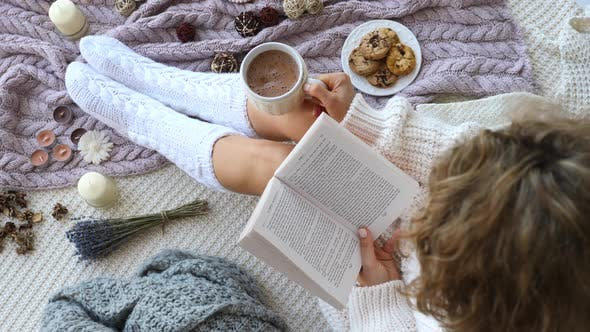 Thumbnail for Woman In Warm Knitted Socks Reading Book And Drinking Hot Chocolate