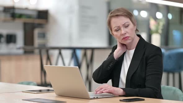 Tired Old Businesswoman Having Neck Pain in Office